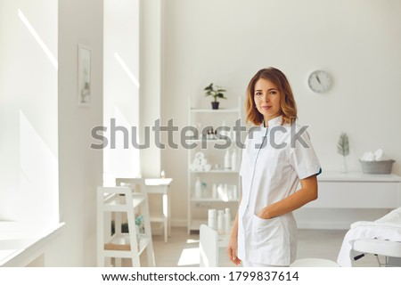 Smiling woman cosmetologist or dermatologist standing and looking at camera in beauty spa salon Foto d'archivio ©
