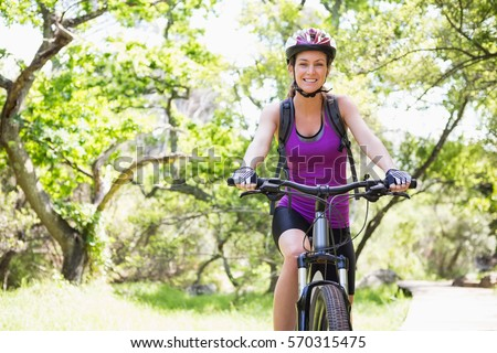 Smiling woman cycling in the countryside