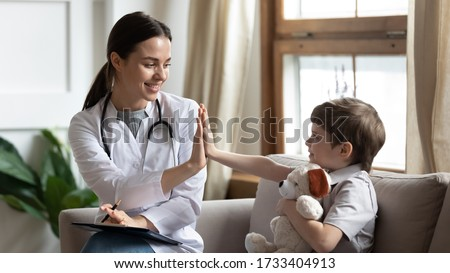Smiling woman doctor or nurse give high five to excited little boy patient at consultation in clinic, happy small child have fun greet with female pediatrician in hospital, healthcare concept