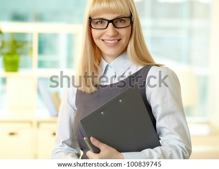 Smiling woman dressed formally looking at cam with a smile and holding a clipboard in her hands