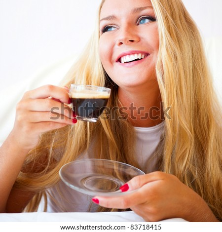 Smiling woman drinking a coffee lying on a sofa at home