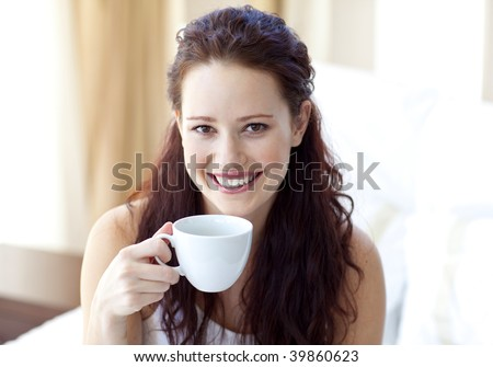 Smiling woman drinking a cup of coffee in bedroom in the morning