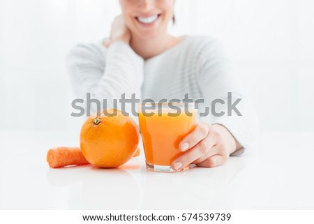 Smiling woman drinking an healthy natural juice made with oranges and carrots, healthy diet and vitamins concept