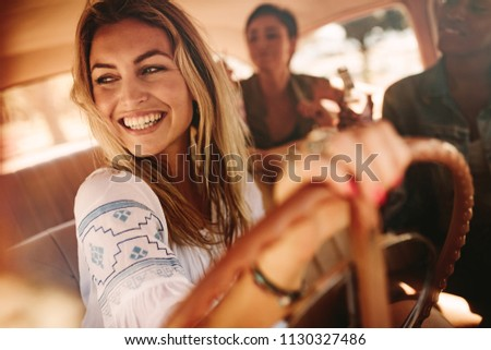 Smiling woman driving a car, going on road trip with friends. Female friends enjoying on a road trip.