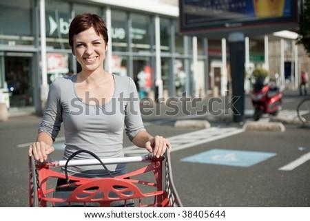 smiling woman driving shopping cart at supermarket car park
