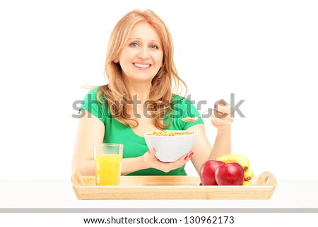 Smiling woman eating cereals and fruit for breakfast isolated on white background