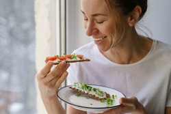 Smiling woman eating rye crisp bread with creamy vegetarian cheese tofu, cherry tomato and rucola micro greens, sitting at home and looking at window. Healthy food, gluten free, diet concept.