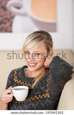 Smiling woman enjoying coffee in a cafe sitting relaxing with a cup of espresso in her hand