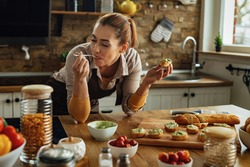 Smiling woman enjoying in taste of healthy food while making avocado bruschetta in the kitchen.