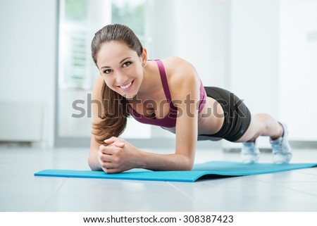 Smiling woman exercising at the gym on a mat, fitness and workout concept