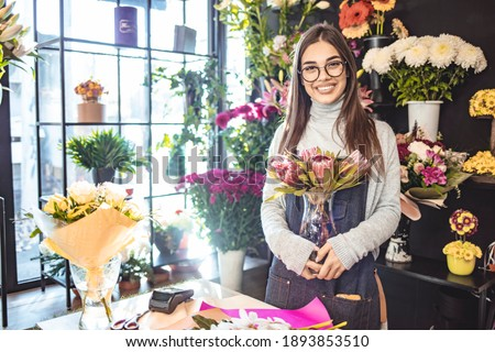 Smiling  Woman Florist Small Business Flower Shop Owner. Happy woman gardener with flower's. Flower's business. Lifestyle flower shop .Flower's shop. Girl with a beautiful flower composition for sale.