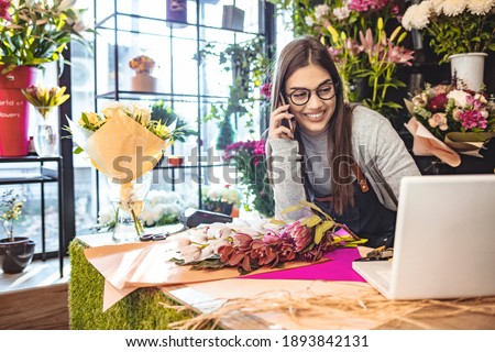 Smiling Woman Florist Small Business Flower Shop Owner. She is using her telephone and laptop to take orders for her store. Female gardener noting client order during mobile phone conversation