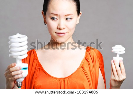 Smiling woman giving energy-saving bulb, isolated on white