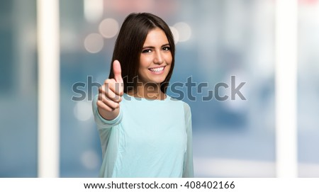 Smiling woman giving thumbs up #408402166
