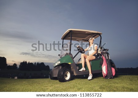 Smiling woman golf player sitting in golf cart at sunset with golf bag and clubs.