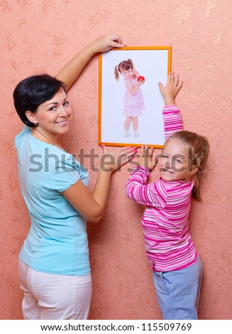 Smiling woman hanging up picture with little girl