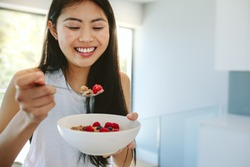 Smiling woman having healthy breakfast at home. Healthy young asian woman in kitchen eating a bowl of nutritious breakfast.