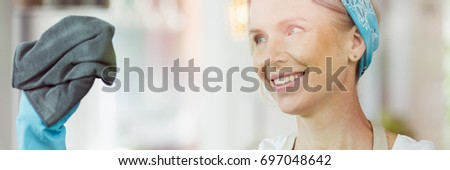 Smiling woman holding a black cloth in her hand and using it to clean a window #697048642