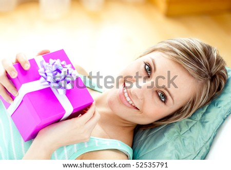 Smiling woman holding a present lying on a sofa - stock photo
