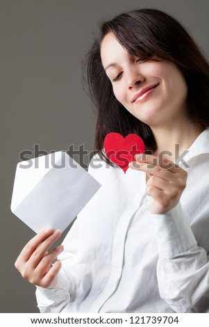 Smiling Woman Holding a Red Heart and an Envelope