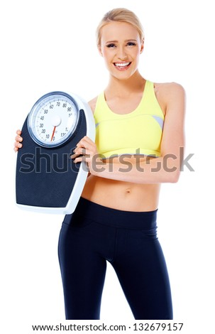 Smiling woman holding a weight scale while posing on white background