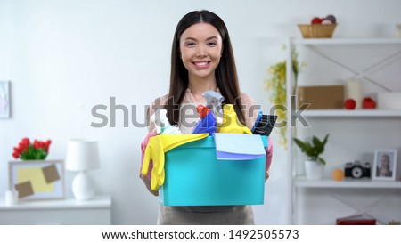 Smiling woman holding basket with detergents, cleaning service, housekeeping #1492505573