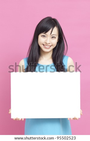Smiling woman holding blank billboard.