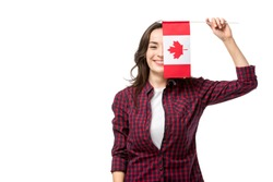 smiling woman holding canadian flag in front of face isolated on white