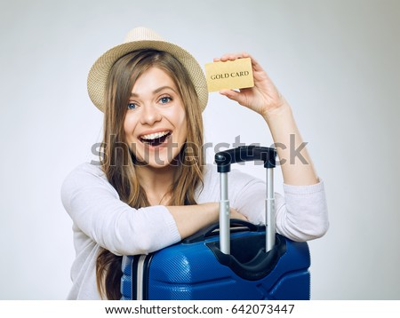 Shutterstock Smiling woman holding credit card. Isolated portrait of girl traveler with suitcase.