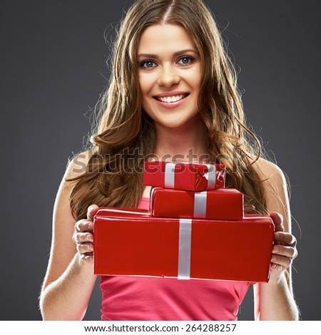 Smiling woman holding gift box. Studio portrait. Young female model.