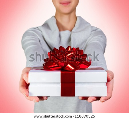 smiling woman holding gift box with red ribbon against pink background