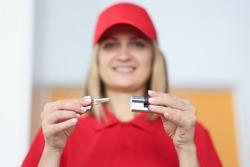 Smiling woman holding key and padlock closeup