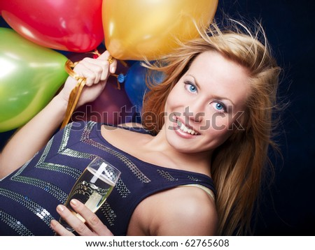 smiling woman holding new year's champagne and balloons over dark background
