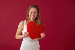Smiling woman holding papper heart in hands on red background. Happy female with symbol of love on valentine's day. Joyful blonde girl with sparkling sign.