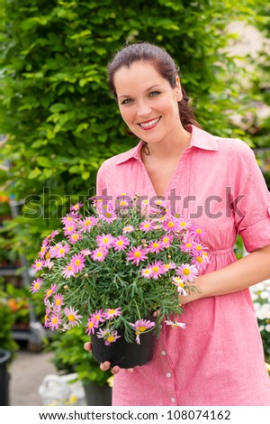 Smiling woman holding pink potted flower in garden center greenhouse