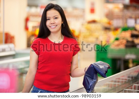 Smiling woman holding product in shopping centre and looking at camera