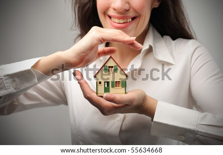 Smiling woman holding the model of a house