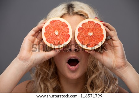 Smiling woman holding two grapefruits in hands
