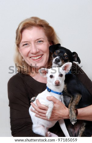 Smiling woman holding two small dogs. Isolated on white.