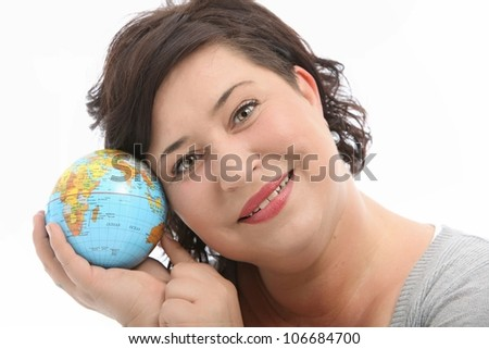 Smiling woman holds a world globe close to her head as she dreams of going on a long vacation sightseeing to wordlwide destinations