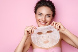 Smiling woman holds facial sheet mask. Photo of attractive woman with perfect skin on pink background. Beauty & Skin care concept