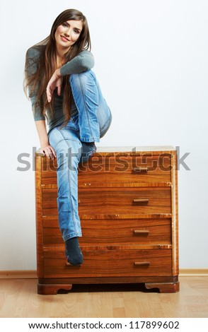 Smiling woman home portrait isolated against white. Young model seating at cupboard for clothes.