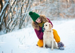 Smiling woman hugging her pet dog golden retriever near face. Golden retriever playing with a woman walking outdoors winter day, warm clothing. love and care for the pet.