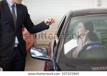 Smiling woman in a car taking keys in a car dealership