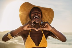 Smiling woman in bikini standing on the beach making a heart shape with her fingers. Female at the seashore wearing a sun hat making heart with hands.