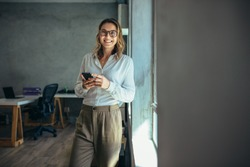 Smiling woman in casuals standing in office. Businesswoman with mobile phone in hand looking at camera.