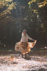 Smiling woman in cozy wear dancing in autumn park in raise of sunlight.