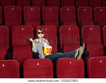Smiling woman in 3D movie theater sitting alone in the row