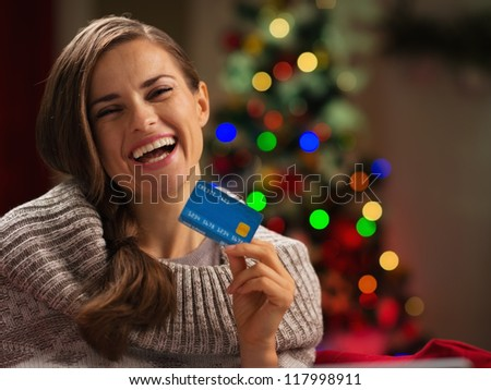 Smiling woman in front of Christmas tree holding credit card