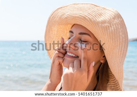 Smiling woman in hat is applying sunscreen on her face. Indian style.